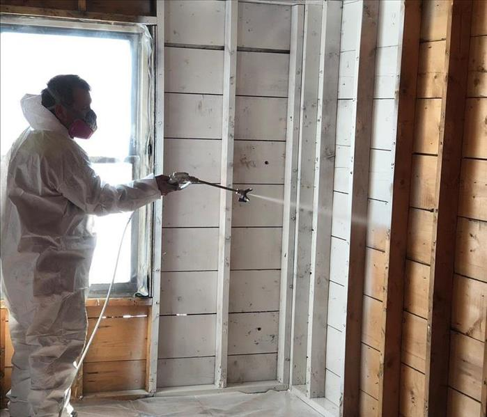 SERVPRO technician in full protective equipment applying paint to corner of deconstructed room with airless sprayer.