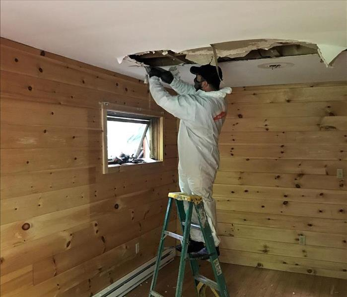 A ceiling with water damage and a SERVPRO technician standing on a ladder
