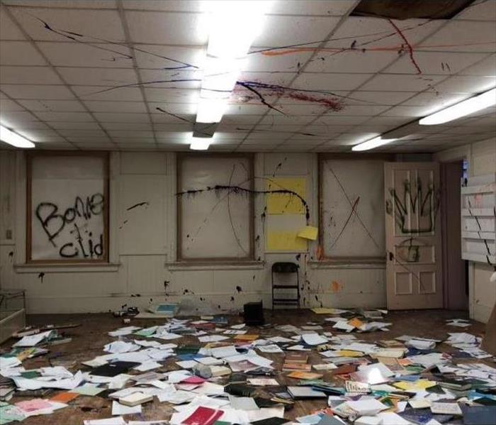 Inside of a commercial space vandalized by spray paint with books and papers scattered throughout the room.
