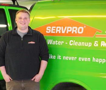 Male SERVPRO employee standing in front of SERVPRO poster and office supplies