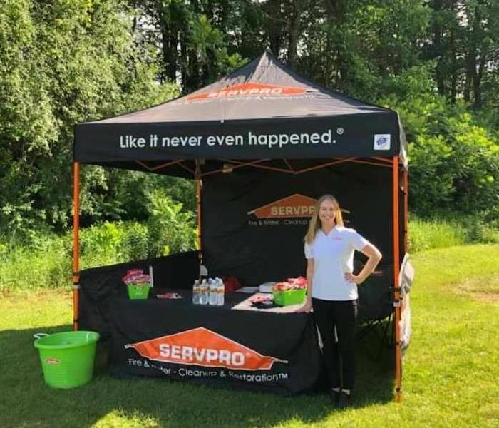 SERVPRO employee standing in front of company tent display on a sunny summer day.