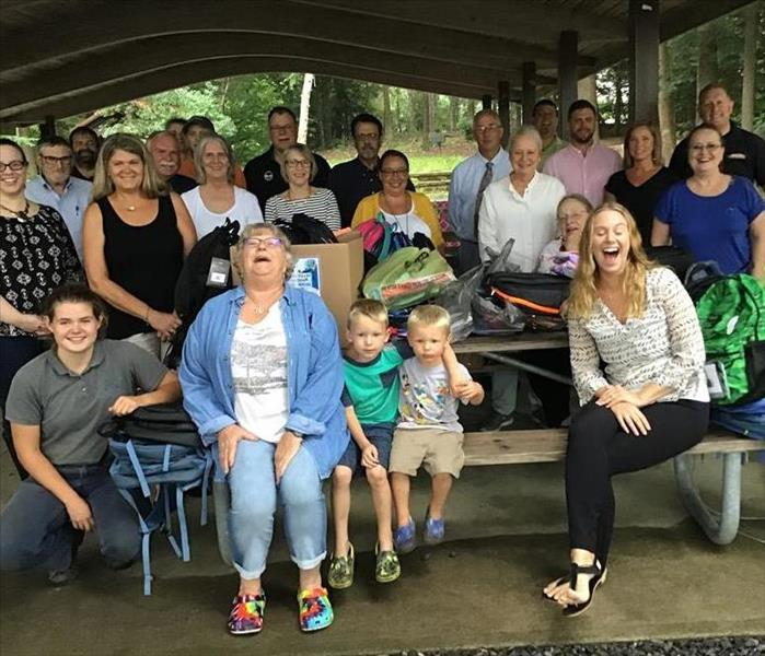 SERVPRO employees along with other members of the realtor board sitting in a covered pavilion with picnic tables
