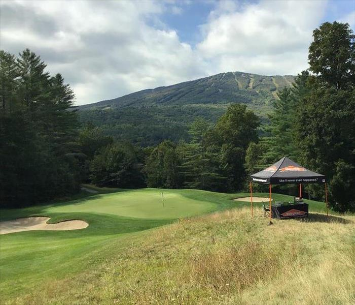 Golf course with black SERVPRO tent and a ski mountain in the distance