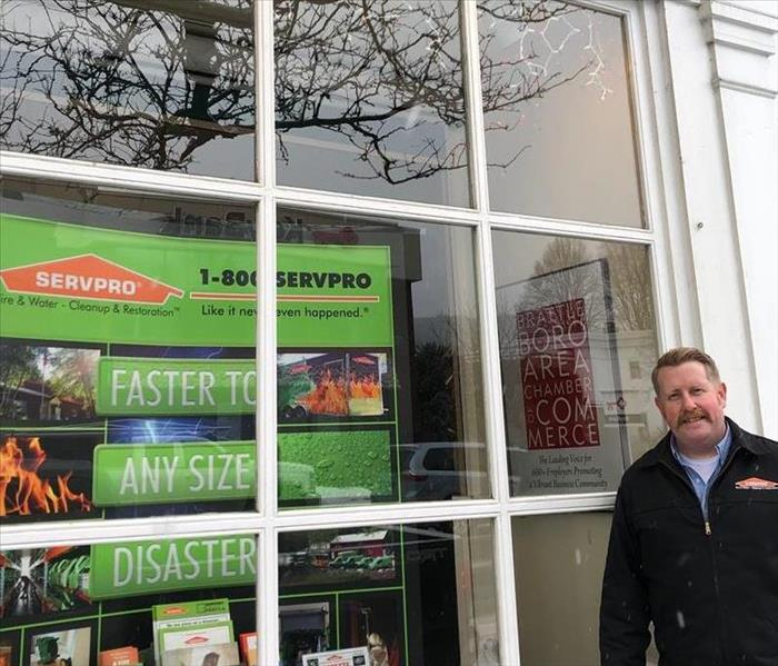 SERVPRO Owner standing in front of a large window display on a street which features a colorful backdrop of his business.