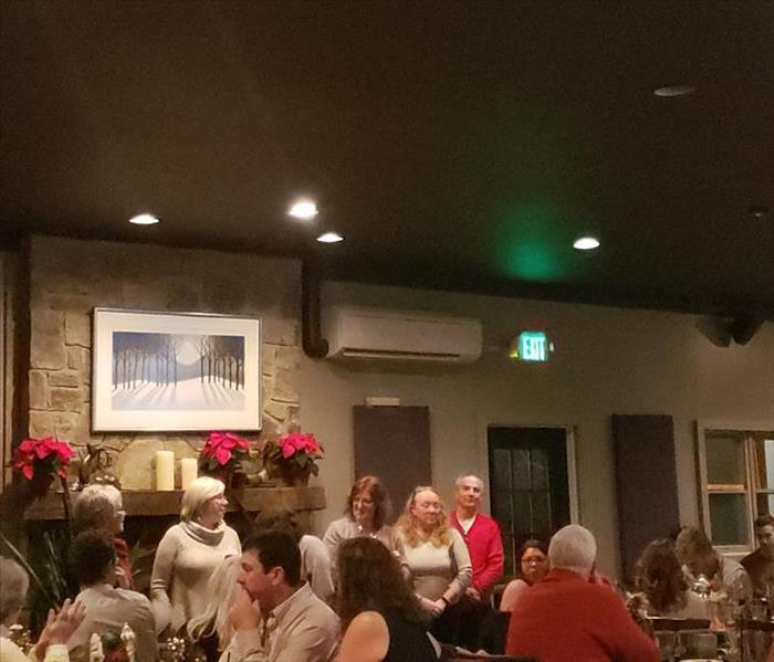 photo of people inside a restaurant, some of them at the front of the room standing and speaking to the group