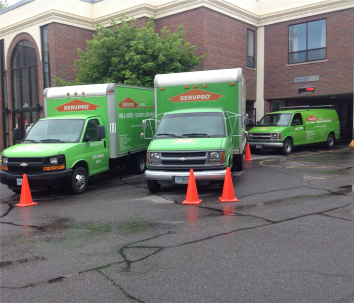 Two green SERVPRO trucks parked in front of a 2-story brick commercial building.