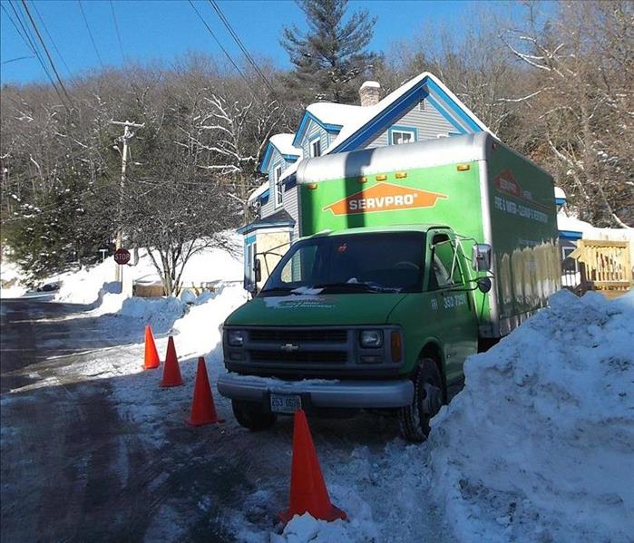 SERVPRO truck parked at a residence surrounded by tall banks of snow.