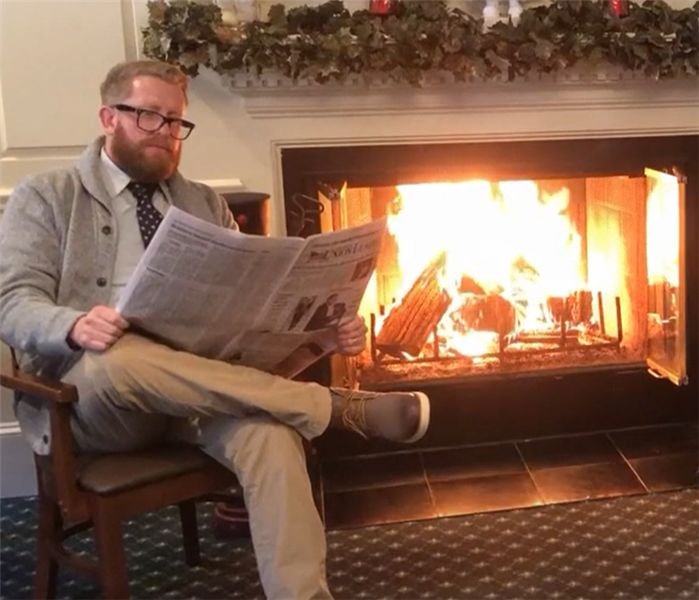 Man with glasses sitting in rocking chair, reading a newspaper next to a roaring fireplace.