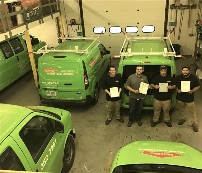 picture of four male SERVPRO employees holding IICRC Certificates and standing in garage with multiple SERVPRO vehicles.