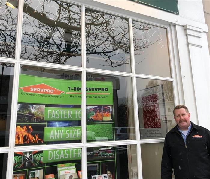 Mustached man wearing a black jacket with SERVPRO logo stands outside a chamber of commerce display window featuring SERVPRO