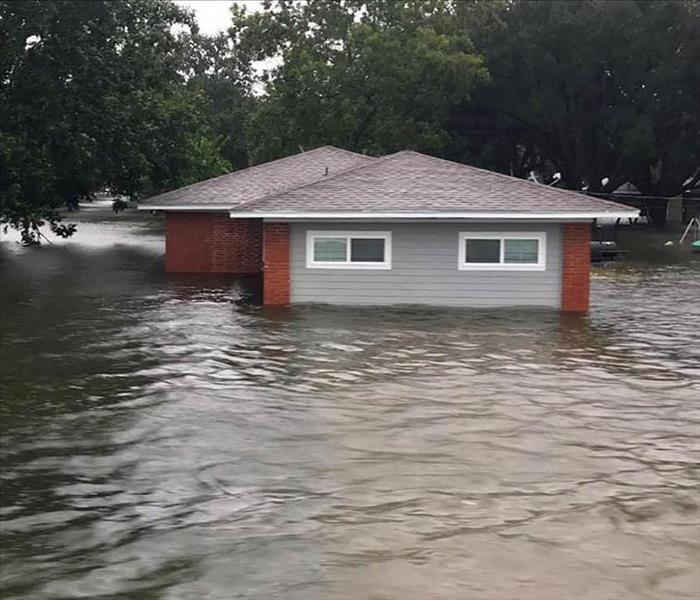 A home almost completely submerged in water during a flood
