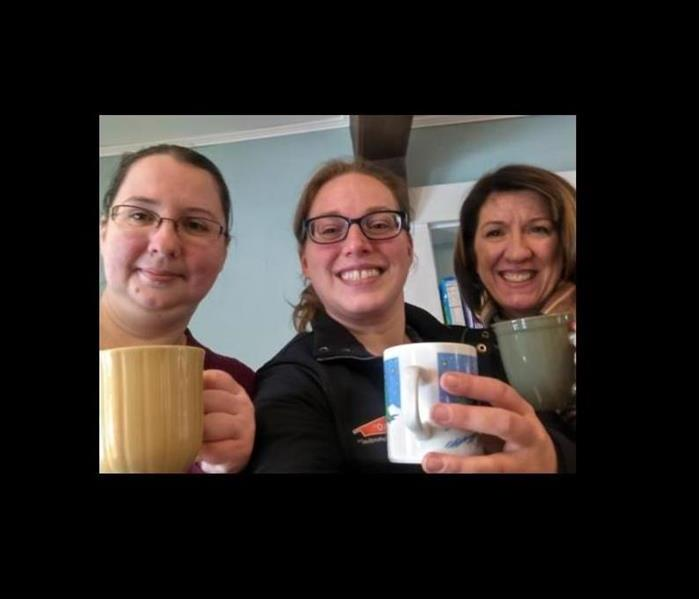 three ladies smiling while holding coffee mugs