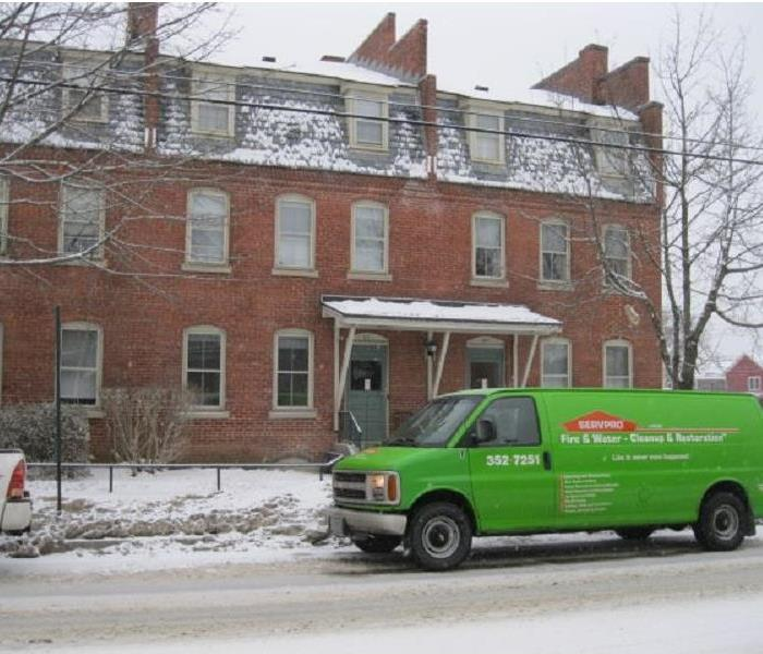SERVPRO truck parked in front of a large brick apartment building with snow on the ground.