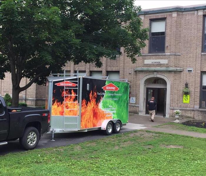 Black pickup truck with SERVPRO Job Trailer attached in front of a large brick school providing emergency services.