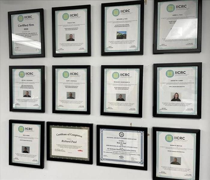 Framed certificates on a white office wall.