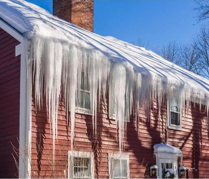 Snow and ice buildup on the edge of a roof on a red house causing large icicles to form.