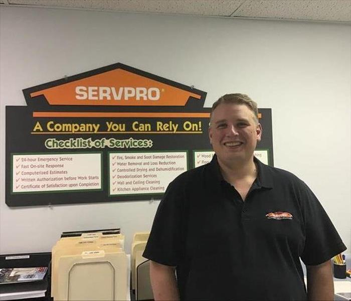 Photo of a SERVPRO employee standing in front of a SERVPRO poster in an office
