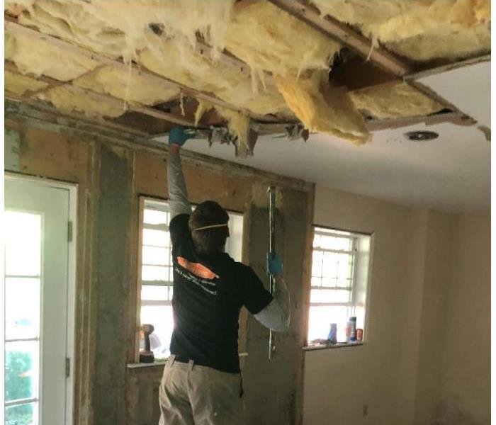 A SERVPRO technician tearing down a ceiling as a result of water damage