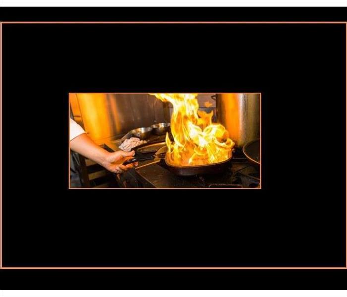 large flames rising from a pan on a range, black background with orange frame